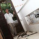 O doté (pai de santo) Amilton Costa mostra porta arrombada por PMs