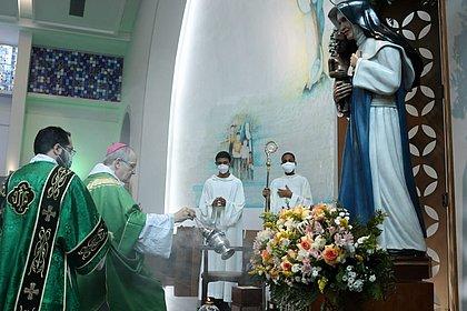 Bispo reverencia a santa durante a missa das 8h30