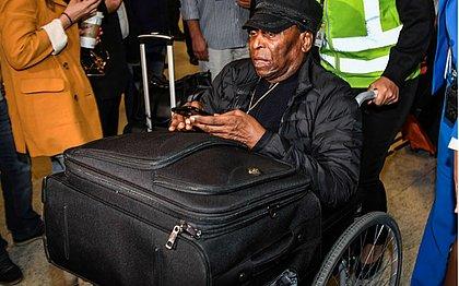 De cadeira de rodas, Pelé desembarca no aeroporto de Guarulhos, em São Paulo