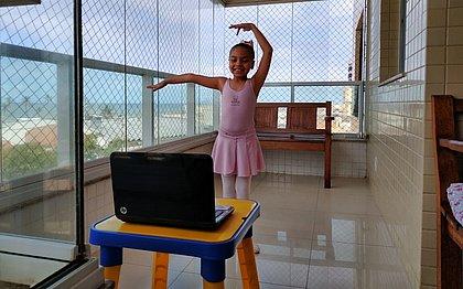 Emanuelle tem sete anos e se diverte com os passos de balé na varanda de casa