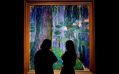 Funcionários de casa de leilões Christie posam com a pintura ' Saule pleureur et bassin aux nymphéas' do pintor impressionista francês Claude Monet, estimado para ser vendido por 40 milhões de libras Esterlinas (52 milhões de USD).