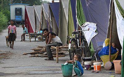 Acampamento improvisado na margem segura do rio Yamuna em Nova Deli. O nível de água do rio aumentou devido à chuva, forçando as famílias que vivem nas áreas baixas do entorno a se deslocarem  para acampamentos.