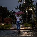 Redescobrindo como ser livre, Carine (nome fictício), na rua onde mora, em uma dia de chuva em Salvador
