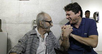 Mario Cravo Jr. brinca com o neto Christian Cravo na abertura da mostra comemorativa