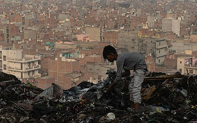 Um jovem indiano coleta material utilizável de um depósito de lixo no aterro Bhalswa em Nova Deli.