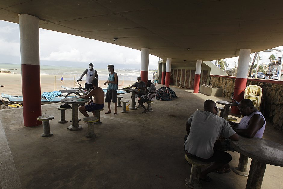 Na Orla de Itapuã, grupos de homens joga cartas em meio às orientações de distanciamento social