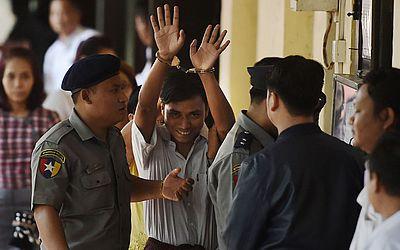 O jornalista de Mianmar Kyaw Soe Oo (C) é escoltado pela polícia para um tribunal em Yangon. Dois jornalistas foram presos por sete anos por violar segredos oficiais.