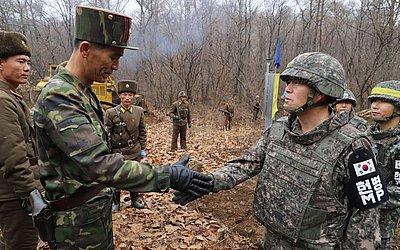 Soldado sul-coreano (D) aperta as mãos de um soldado norte-coreano perto da linha de demarcação militar (placa amarela) durante uma recente operação para construir uma estrada tática.