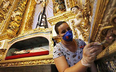 Restauradora dá os últimos retoques na capela do santíssimo.