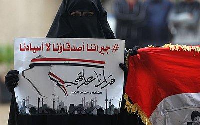 """Uma mulher iraquiana leva um cartaz """"nossos vizinhos são nossos amigos, mas não nossos mestres."""", em Bagdá Sadr City em manifestação para que governo iraquiano acelera sua formação sem influêbncias externas."""