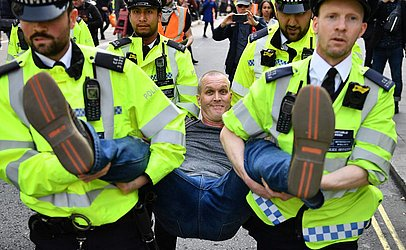 Polícia prende uma ativista que estava bloqueando Oxford Circus, no terceiro dia de um protesto ambiental pelo grupo Extinction Rebellion em Londres.