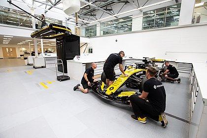 Técnicos da Renault movimentam um dos carros de teste na sede da equipe na Inglaterra
