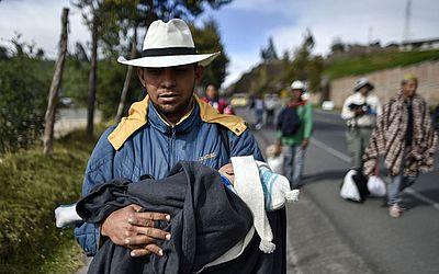 O venezuelano Richard Lomelle e seu bebê Tiago caminham ao longo da rodovia Pan-americana, entre Pasto e Ipiales, Colombia, no caminho para o Peru