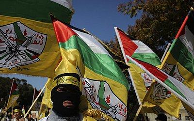 Partidários do grupo palestino Fatah durante uma marcha comemorativa ao 54º aniversário da criação do partido, na cidade ocupada da Cisjordânia, em Nablus.