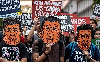 Manifestantes usam máscaras do Presidente, Xi Jinping da China, durante um protesto em Manila, contra sua visita as Filipinas.