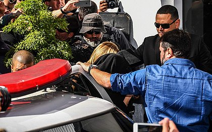 Najila, coberta com um casaco preto, chega à delegacia em São Paulo