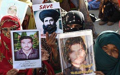 Parentes de desaparecidos paquistaneses levam fotos de seus entes queridos em uma manifestação pelos direitos humanos em Quetta, na província de Baluchistão.