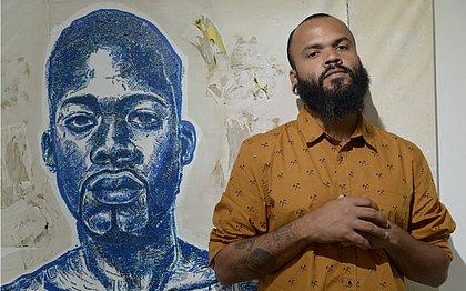 SuperAfro ao lado de um retrato que fez do irmão, Elielson