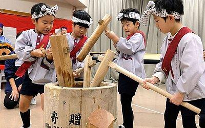 Crianças japonesas usam martelos de madeira para sovar o arroz cozido no vapor para feitura do bolo de arroz mochi durante o evento anual de mochi-tsuki para celebrar o ano novo em um jardim de infância em Tóquio.