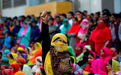 Trabalhadores da indústria de confecção de Bangladeshi bloqueiam uma estrada durante uma manifestação para exigir melhores salários em Dhaka. A polícia usou 9 canhões de água para para dispersar os 10.000 trabalhadores.