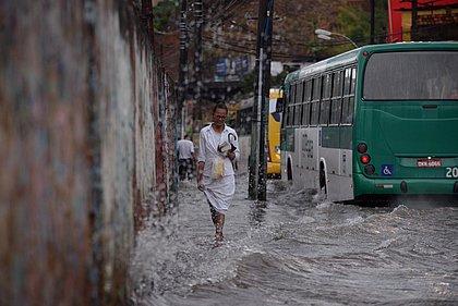Pedestre tenta desviar do banho de água suja deixado pelos veículos que transitam na Rua