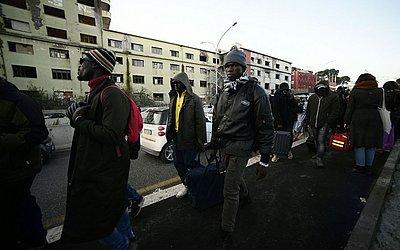 40 imigrantes de várias nacionalidades da África carregando seus pertences são evacuados de uma fábrica de penicilina onde viviam junto a alguns italianos viviam em condições precárias.