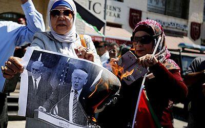 Palestinas queimam fotos do presidente americano Donald Trump e do primeiro-ministro israelense, Benjamin Netanyahu, durante uma manifestação para protestar contra os cortes de verba humanitária para os palestinos.
