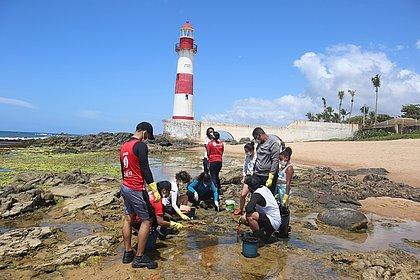 Crianças, homens, mulheres fazem 'trabalho de formiguinha' em Itapuã