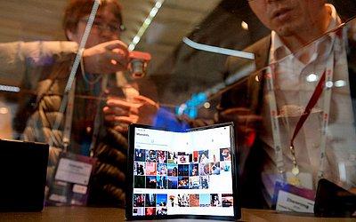 Visitantes olham o novo celular dobrável no Mobile World Congress (MWC), em Barcelona.