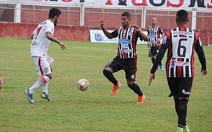 Atleticano Mailson tenta o drible diante do jogador do Villa Nova