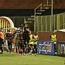 Nos braços dos outros jogadores, Eduardo comemora gol da classificação do Vitória