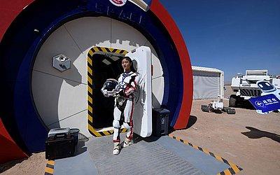 "Guia vestindo traje espacial na entrada da ""Base Marte 1"", no deserto de Gobi, cerca de 40 quilómetros de Jinchang na província de Gansu noroeste da China."