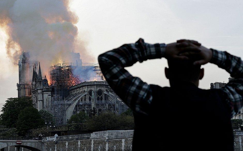 Homem observa o incêndio na igreja