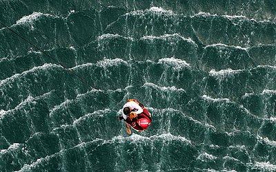 """Um salva-vidas voluntário participa de uma simulação de resgate durante o 54ª  """"Paso del Hombre"""", desafio aquático de resistência organizado pela Cruz Vermelha salvadorenha, em La Libertad, El Salvador."""