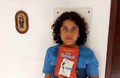 Yalle posa para a foto com um de seus livros favoritos: O Diário de um Banana