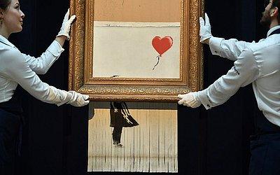 """Trabalho recém concluído de Banksy, intitulado """"O Amor está na lixeira"""", que consiste no quadro """"Menina com balão"""" passado através de uma trituradora de papel em uma intervenção surpresa na casa de leilões Sotheby em Londres."""