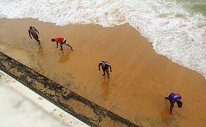 Homens catavam moedas, correntes e outros objetos trazidos pelo mar na Barra.