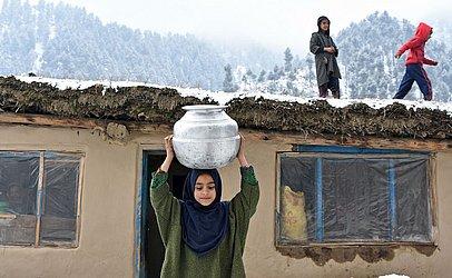 Garota da Caxemira carrega um pote de água nos arredores de Srinagar.