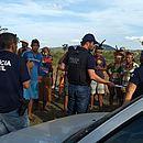 Policiais civis conversam com grupo em fazenda, durante operação