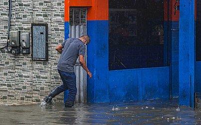 Comerciantes tentavam barrar a entrada da água.