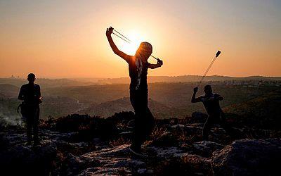 Manifestantes palestinos arremessam pedras durante confrontos com as forças de segurança israelenses na vila de Ras Karkar a oeste de Ramallah na Cisjordânia ocupada.