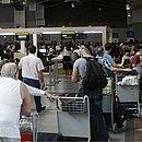 Passageiros aguardam em filas enormes no salão do aeroporto