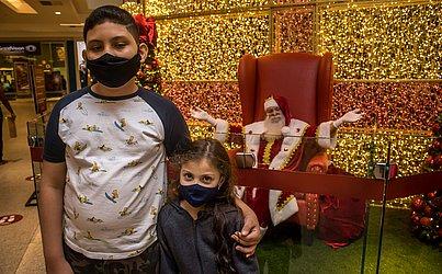 Papai Noel deu um jeitinho de aparecer durante a pandemia. O bom velhinho fica protegido atrás de um muro de vidro.