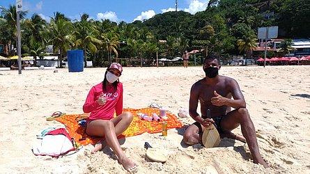 A enfermeira soteropolitana Lídia França, 25, e o recepcionista Iago Rocha, 24, usam máscara na praia e escolheram cantinho isolado em Morro de SP