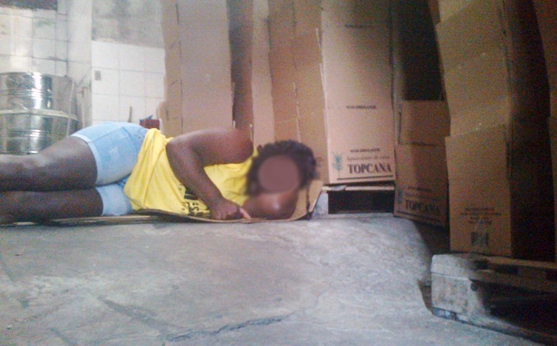 Funcionária dormindo no chão, em meio a caixas de Topcana