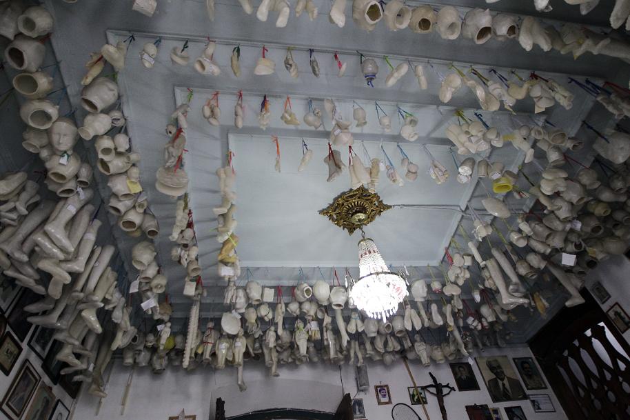 Sala de ex-votos com diversas peças de cera e madeira