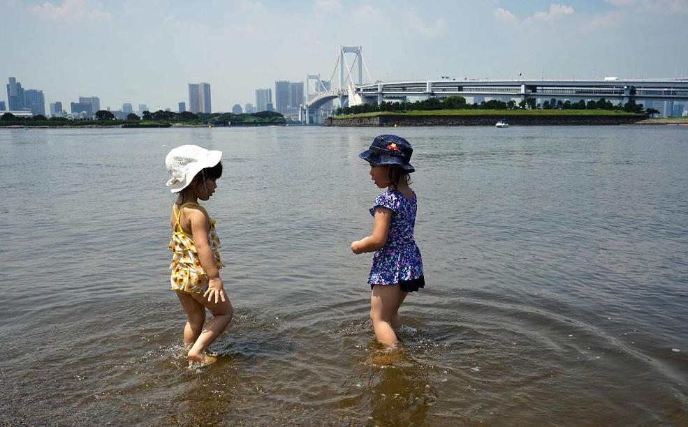 Crianças se refrescam em dia de calor em Tóquio.