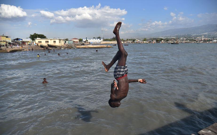 Menino mergulha em Soleil Wharf, em Cité Soleil, Porto Príncipe.