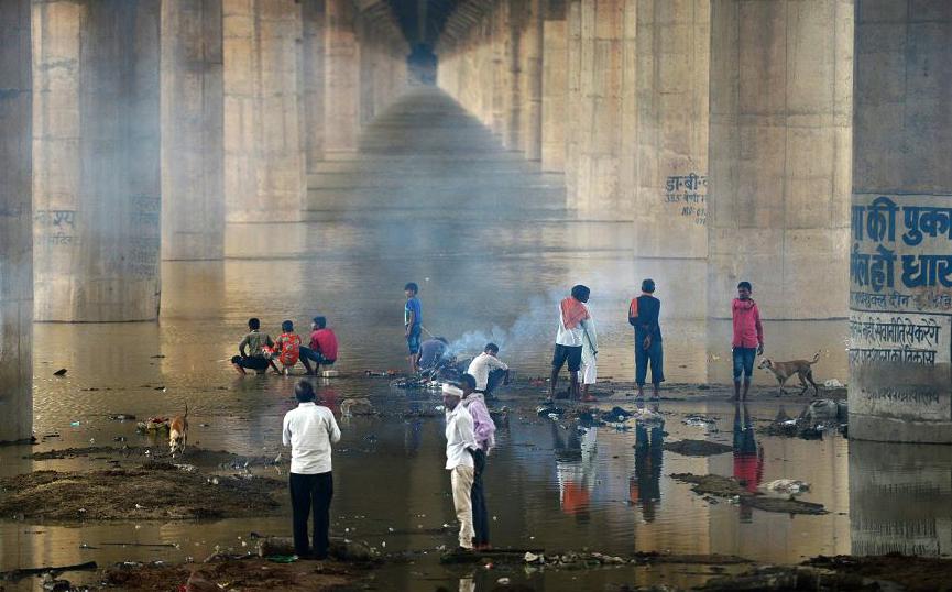 Indianos cremam um corpo perto do rio Ganges sob a ponte Shastri no Daraganj ghat, em Allahabad. Os níveis de água dos rios Ganges e Yamuna aumentaram enormemente com as chuvas de monção.