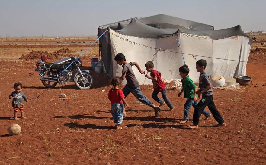 Crianças sírias jogam bola fora da tenda do acampamento da aldeia de Surman, na província de Idlib.